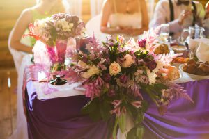 a table at a wedding decorated with flowers and set with catered food.
