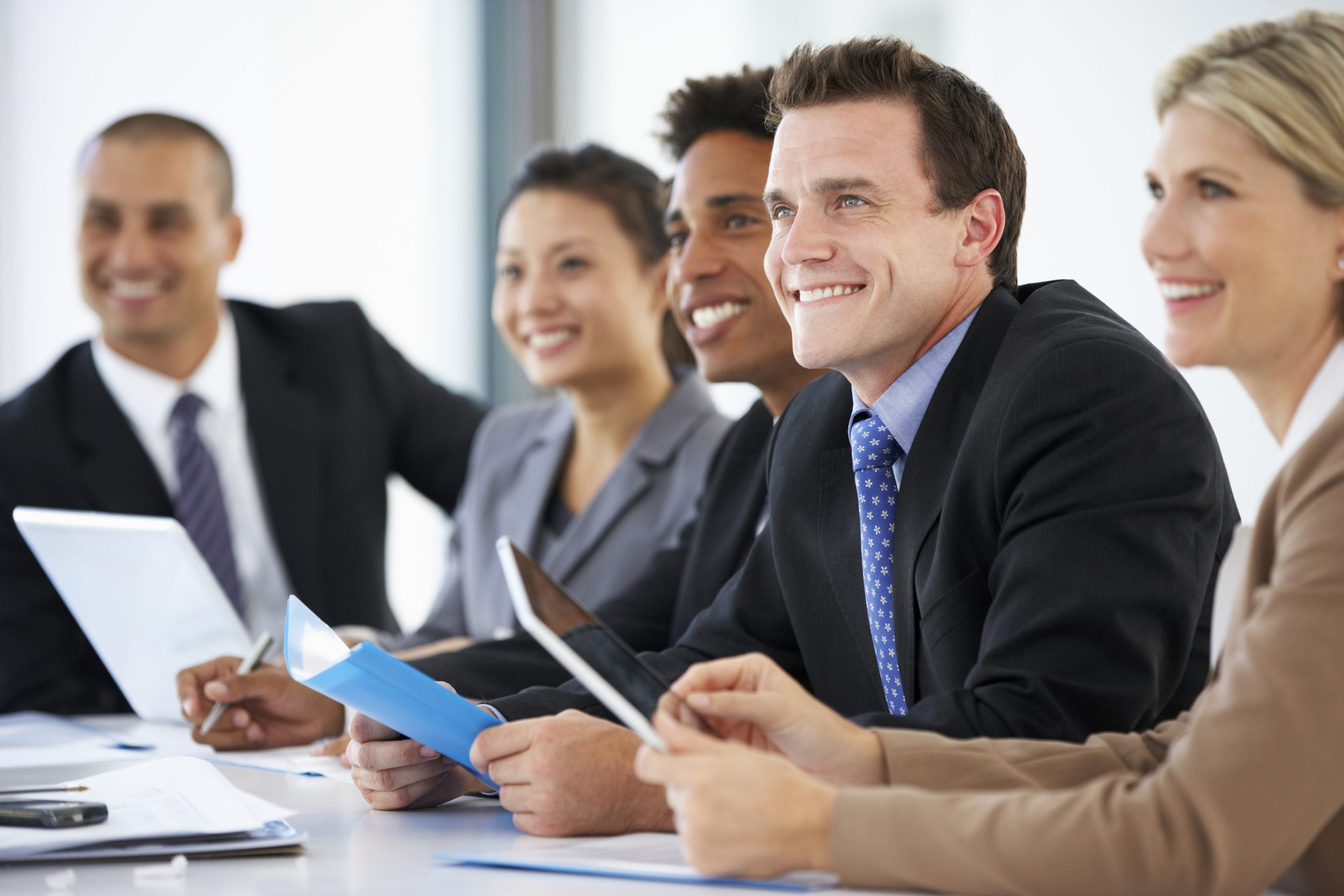 employees sitting at a conference table at in a meeting