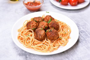 Meatballs in tomato sauce and spaghetti close up view